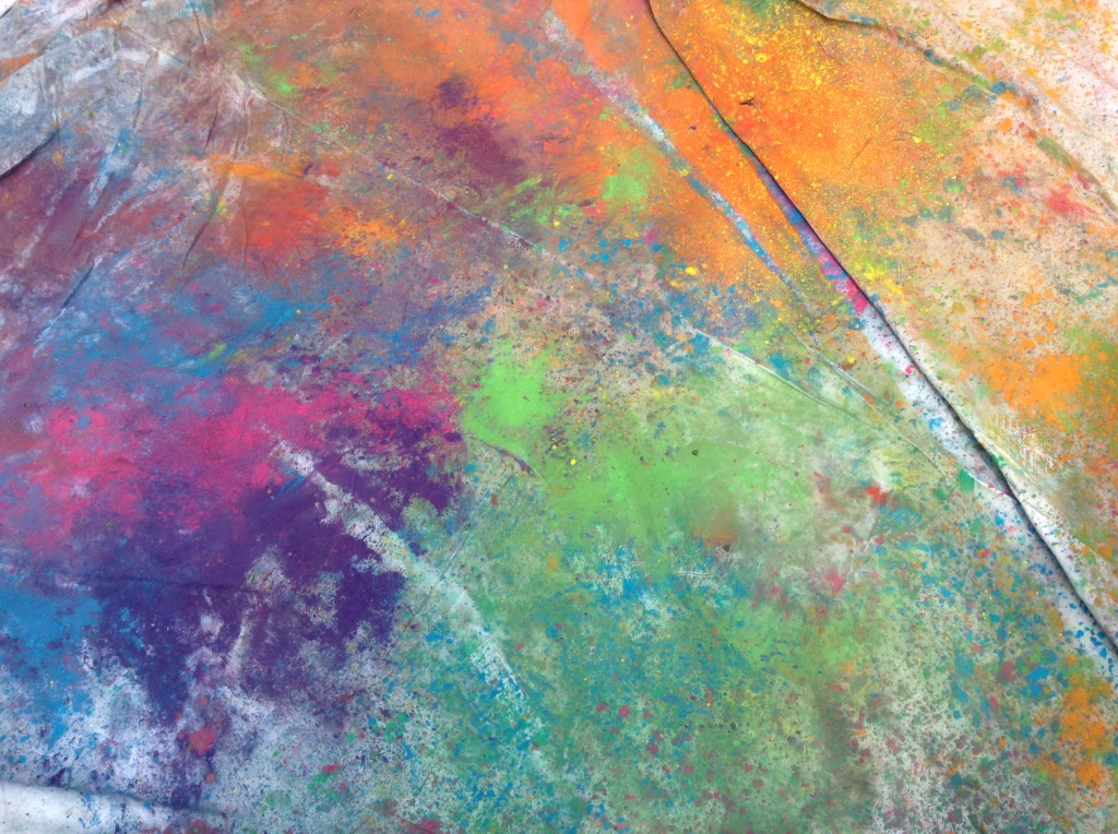 Celebrating Holi with Kids at home with a white sheet to throw color on