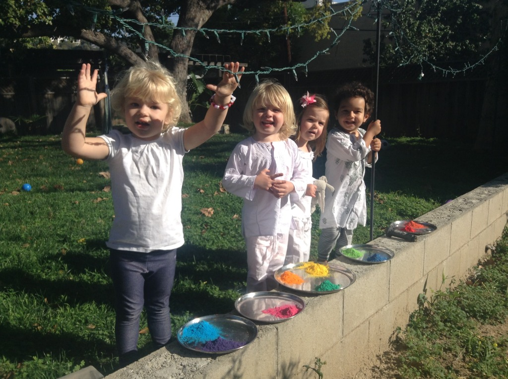 Kids celebrating holi with plates of color
