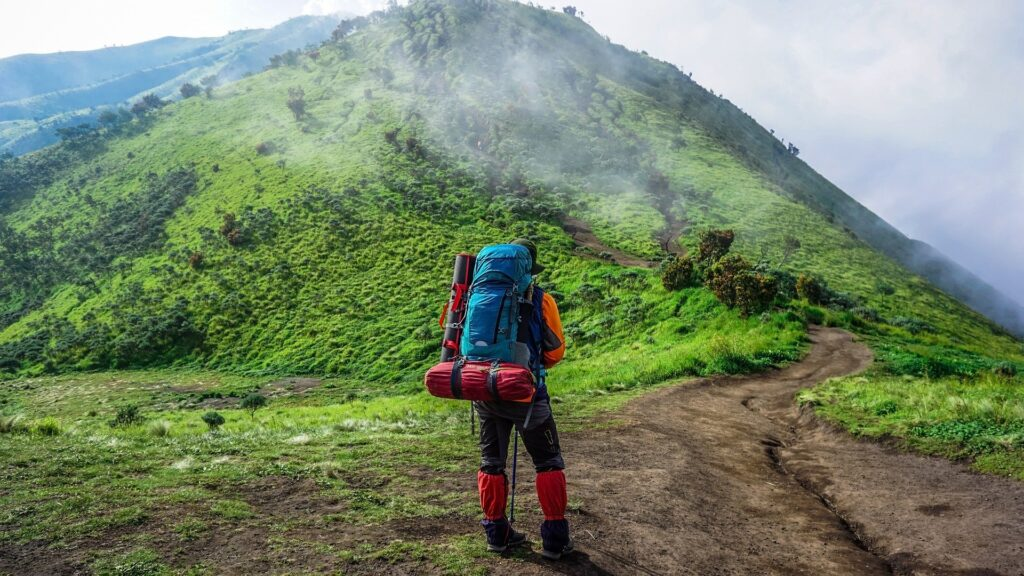 Backpacker with backpack heading out on a green mountain hike